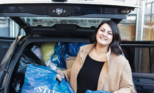 Jasmine Topham, founder of Bundle Up YEG unloading her car with goods for Bissell Centre.